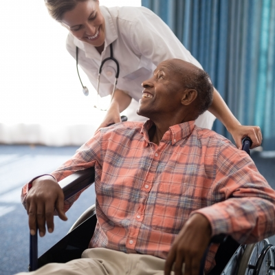 Smiling female doctor looking at disabled senior man sitting on wheelchair against window in retirement home