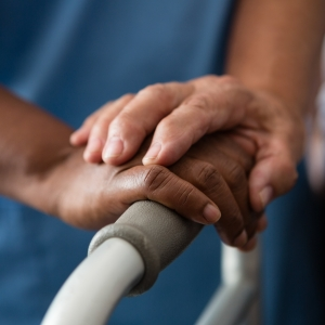 Cropped hands of nurse and senior woman holding walker in nursing home
