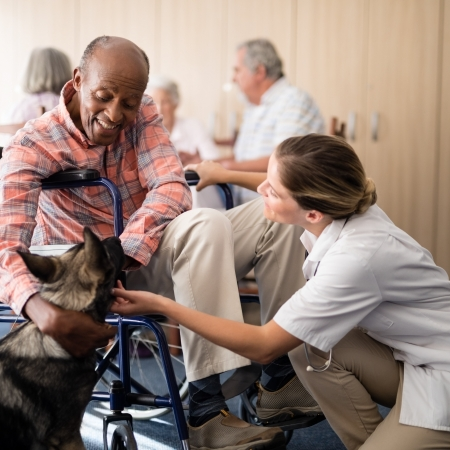 Cheerful female doctor kneeling by disabled senior man stroking puppy at retirement home